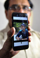 Indian man Jagan Mohan Reddy holds a smartphone with an image of his son Alok Madasani at his residence in Hyderabad on February 24, 2017, after Alok was injured in a shooting in the US state of Kansas. Alok and his friend Srinivas Kuchibhotla were in a bar in Kansas when a man allegedly yelled 'get out of my country' before shooting at them. Mr Kuchibhotla was killed and Alok is injured and is undergoing treatment in hospital.