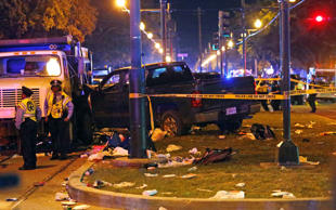 Police stand next to a pickup truck that slammed into a crowd and other vehicles...