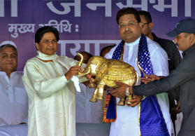 Mayawati (2nd L), chief of Bahujan Samaj Party (BSP), receives a model of an ele...
