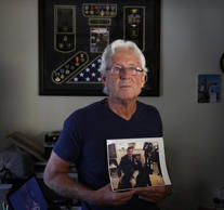 William Owens, clutching a photo of son Ryan, the SEAL killed in a January commando raid, says the administration is wrong to say that anyone who questions the raid does his son a disservice.