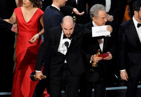HOLLYWOOD, CA - FEBRUARY 26:  'La La Land' producer Jordan Horowitz holds up the winner card reading actual Best Picture winner 'Moonlight' with actor Warren Beatty onstage during the 89th Annual Academy Awards at Hollywood & Highland Center on February