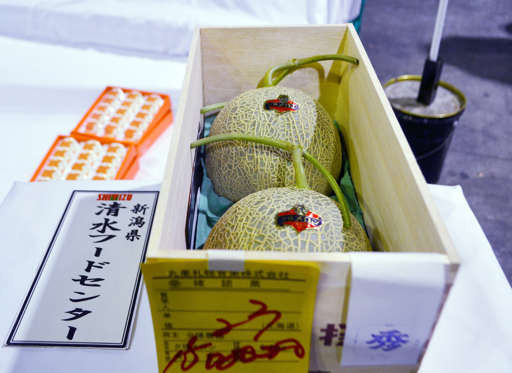 الشريحة 11 من 13: A woman points at a pair of Japanese Yubari melons displayed under a sign indicating a price of 1 million yen