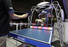 A staff member plays table tennis with Omron Corp.'s table tennis robot FORPHEUS during the annual CEATEC Japan advanced technologies show in Chiba Thursday, Oct. 6, 2016.