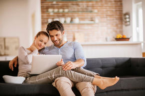 Close up of a happy young couple using laptop at home.