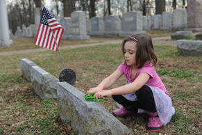 A young child cleans a headstone during a cleanup effort at Chesed Shel Emeth Cemetery on February 22, 2017 in University City, Missouri. Missouri Gov.