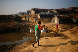 A Rohingya refugee man carries water on his shoulder in the morning at Kutupalang Unregistered Refugee Camp in Cox's Bazar, Bangladesh, on February 4, 2017.