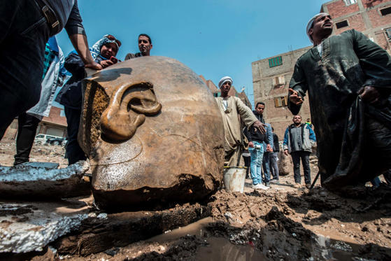 Slide 1 of 14: Egyptian workers look at the site of a new discovery by a team of German-Egyptian archeologists in Cairo's Mattarya district on March 9, 2017. Statues of the kings and queens of the nineteenth dynasty (1295 - 1185 BC) were unearthed in the vicinity of th