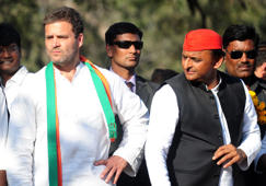 Chief Minister of the northern Indian state of Uttar Pradesh and Samajwadi Party leader Akhilesh Yadav (R) and Congress Party vice- President Rahul Gandhi (L) speak as they take part in a joint roadshow in support of their state assembly election party candidates in Allahabad