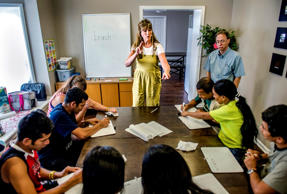 The Rev. Debbie Buchholz, center, leads an American Sign Language class for deaf refugees in Kansas City, Kan. Near Buchholz is volunteer tutor John Kingsley, right. Buchholz, who is hard of hearing herself, runs a program for deaf refugees through her Olathe church. (Allison Long/Kansas City Star/TNS via Getty Images)