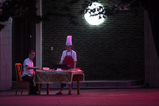 Slajd 2 z 100: A photo taken on July 22, 2017 shows a man eating at a table outside a restaurant in Pyongyang.