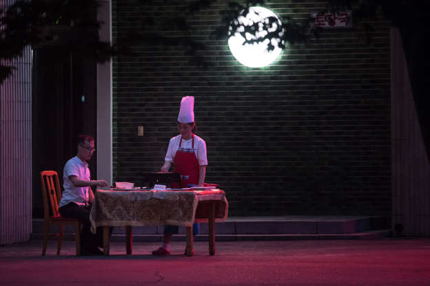 Slide 2 of 99: A photo taken on July 22, 2017 shows a man eating at a table outside a restaurant in Pyongyang.