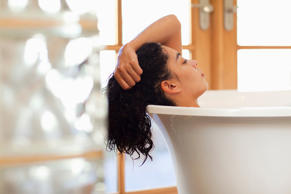 Mixed race woman soaking in bathtub