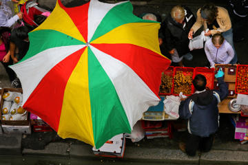 A sidewalk fruit vendor does brisk business under an umbrella on Beach Street in Boston's Chinatown neighborhood on Jul. 25, 2017.