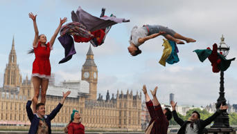 Circus artists perform a stunt opposite the Houses of Parliament to announce the official launch of Circus250 in London, Tuesday, July 25, 2017.(AP Photo/Frank Augstein)