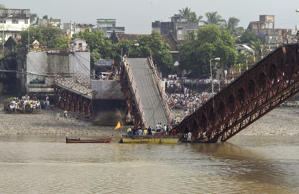 People gather to see rescue work near a collapsed bridge in Daman, 190 kilometers (120 miles) north of Bombay, India, Friday, Aug. 29, 2003. At least 12 people, including eight school children, were killed Thursday when a school van, two rickshaws and motorcycles plunged into a river after the concrete bridge collapsed in western India.