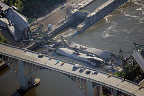 The Interstate-35W freeway bridge is seen collapsed in the Mississippi River in downtown Minneapolis, Thursday, Aug. 2, 2007. Divers searched the Mississippi River Thursday for more bodies entombed in cars trapped beneath the twisted steel and concrete slabs of a bridge that collapsed Wednesday, killing at least four.