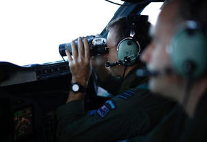 Wing Commander Rob Shearer looks through binoculars on the flight deck of a Royal New Zealand Air Force P-3K2 Orion aircraft searching for missing Malaysian Airlines flight MH370 on March 29, 2014