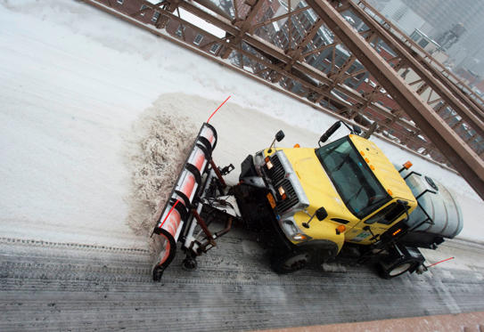 Slide 1 of 27: A snowplow clears snow from the Brooklyn Bridge March 14, 2017 in New York.