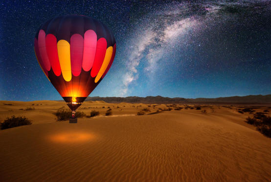 Slide 1 of 38: A majestic hot air balloon soars under the stars of the Milky Way, over the desert - Mesquite Dunes of Death Valley National Park. Moonlight provides luminosity showing the patterns and shapes of the desert landscape.