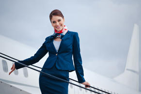 Outdoor portrait of a beautiful flight attendant standing on the aircraft stairs and smiling at the camera.