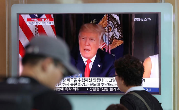 People walk by a TV screen showing a local news program reporting with an image of U.S. President Donald Trump at the Seoul Train Station in Seoul, South Korea, Wednesday, Aug. 9, 2017.
