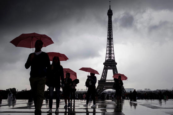 Slide 1 of 42: Tourists walk with umbrellas at Trocadero near the Eiffel Tower as it rains in Paris on August 10, 2017.