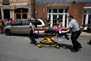 "Rescue workers transport a victim who was injured when a car drove through a group of counter protestors at the ""Unite the Right"" rally Charlottesville, Virginia, U.S., August 12, 2017."