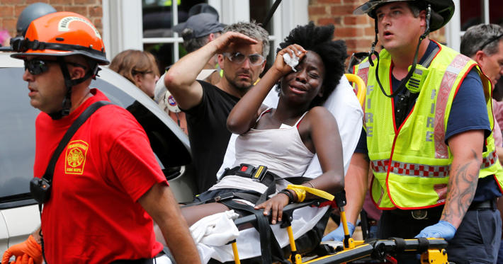 Slide 1 of 40: Rescue personnel help an injured woman after a car ran into a large group of protesters after an white nationalist rally in Charlottesville, Va., Saturday, Aug. 12, 2017. The nationalists were holding the rally to protest plans by the city of Charlottesville to remove a statue of Confederate Gen. Robert E. Lee. There were several hundred protesters marching in a long line when the car drove into a group of them.()