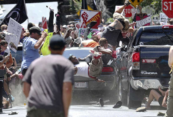 Slide 4 of 40: People fly into the air as a vehicle drives into a group of protesters demonstrating against a white nationalist rally in Charlottesville, Va., Saturday, Aug. 12, 2017. The nationalists were holding the rally to protest plans by the city of Charlottesville to remove a statue of Confederate Gen. Robert E. Lee. There were several hundred protesters marching in a long line when the car drove into a group of them.