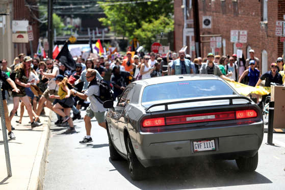 Slide 2 of 40: A vehicle drives into a group of protesters demonstrating against a white nationalist rally in Charlottesville, Va., Saturday, Aug. 12, 2017. The nationalists were holding the rally to protest plans by the city of Charlottesville to remove a statue of Confederate Gen. Robert E. Lee. There were several hundred protesters marching in a long line when the car drove into a group of them.