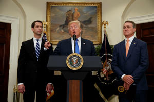 President Donald Trump, flanked by Sen. Tom Cotton, R- Ark., left, and Sen. David Perdue, R-Ga., speaks in the Roosevelt Room of the White House in Washington, Wednesday, Aug. 2, 2017, during the unveiling of legislation that would place new limits on legal immigration.