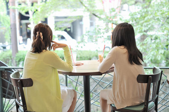 Slide 1 of 11: Two women are relaxing in a cafe.