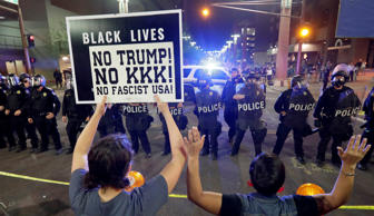 Protesters raise their hands after Phoenix police used tear gas outside the Phoe...
