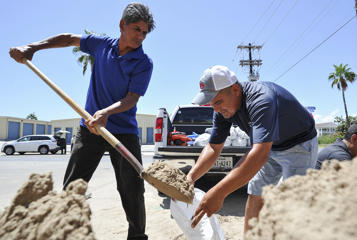 Leo Sermiento, left, and Emilio Gutierrez, right, fill sandbags in preparation of a tropical system on Wednesday, Aug. 23, 2017, on South Padre Island, Texas. Texas Gov. Greg Abbott has ordered the State Operations Center to elevate its readiness level and is making state resources available for preparation and possible rescue and recovery actions amid forecasts a tropical storm will make landfall along the Texas Gulf Coast.