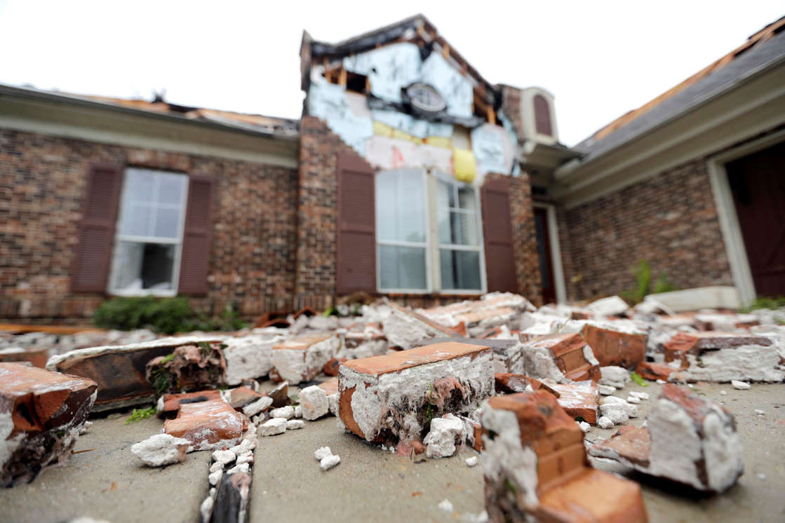 Slide 32 of 77: Fallen bricks from a home damaged by Hurricane Harvey sit on the ground Saturday, Aug. 26, 2017, in Missouri City, Texas.  Harvey rolled over the Texas Gulf Coast on Saturday, smashing homes and businesses and lashing the shore with wind and rain so intense that drivers were forced off the road because they could not see in front of them.