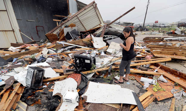 Slide 1 of 65: Jennifer Bryant looks over the debris from her family business destroyed by Hurricane Harvey Saturday, Aug. 26, 2017, in Katy, Texas. Harvey rolled over the Texas Gulf Coast on Saturday, smashing homes and businesses and lashing the shore with wind and rain so intense that drivers were forced off the road because they could not see in front of them.