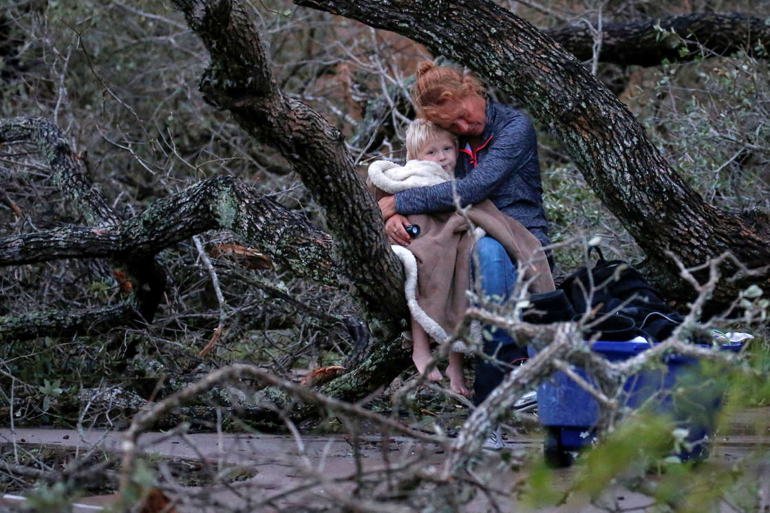 Slide 9 of 77: Lisa Rehr holds her four-year old son Maximus, after they lost their home to Hurricane Harvey, as they await to be evacuated with their belongings from Rockport, Texas, U.S. August 26, 2017.
