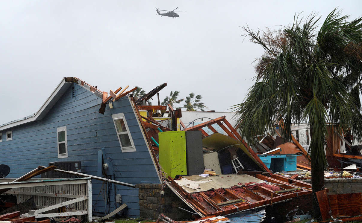 Slide 7 of 77: A military helicopter flies over a destroyed house after Hurricane Harvey struck in Rockport, Texas, August 26, 2017.