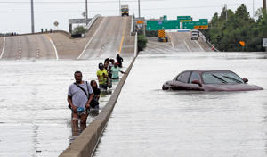 Evacuees wade down a flooded section of Interstate 610 as floodwaters from Tropical Storm Harvey rise Sunday, Aug. 27, 2017, in Houston. The remnants of Hurricane Harvey sent devastating floods pouring into Houston Sunday as rising water chased thousands of people to rooftops or higher ground.