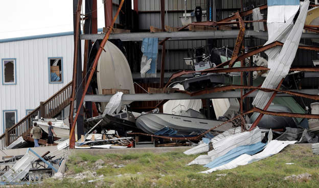 Slide 2 of 92: Two men check out damage to a boat storage facility caused by the effects of Hurricane Harvey, Sunday, Aug. 27, 2017, in Rockport, Texas. (AP Photo/Eric Gay)