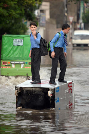 Pakistani students stand on a waste container lying on a flooded street after heavy monsoon rains hit the city of Rawalpindi, Pakistan on August 25, 2017.
