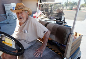 Dr. Charles Thomson, 92, of Sun City, Ariz., gets in his golf cart after talking...