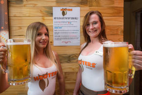 JOHANNESBURG, SOUTH AFRICA JANUARY 16: (SOUTH AFRICA OUT): Hooters Girls; Yana Aerts and Hailey Sprenger hold beers in front of the Angel shot poster at Hooters Restaurant on January 16, 2017 in Johannesburg, South Africa. The Angel shot poster is a drinks menu designed for women to safely communicate to restaurant assistant when they feel threatened or unsafe, by ordering specific signal drinks.