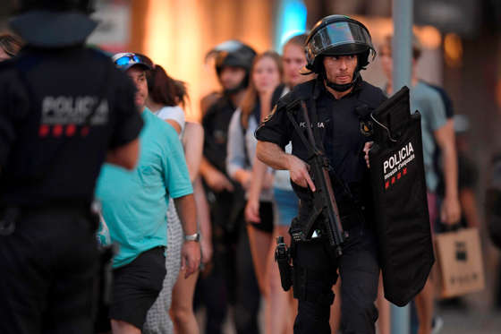 """Slide 2 of 19: Spanish policemen stand guard in a cordoned off area after a van ploughed into the crowd, killing 13 persons and injuring over 50 on the Rambla in Barcelona on August 17, 2017. A driver deliberately rammed a van into a crowd on Barcelona's most popular street on August 17, 2017 killing at least 13 people before fleeing to a nearby bar, police said. Officers in Spain's second-largest city said the ramming on Las Ramblas was a """"terrorist attack"""" and a police source said one suspect had left the scene and was """"holed up in a bar"""". The police source said they were hunting for a total of two suspects. / AFP PHOTO / LLUIS GENE (Photo credit should read LLUIS GENE/AFP/Getty Images)"""