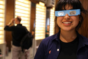 Warby Parker employee Karolyna Landin poses with a pair of solar eclipse glasses...