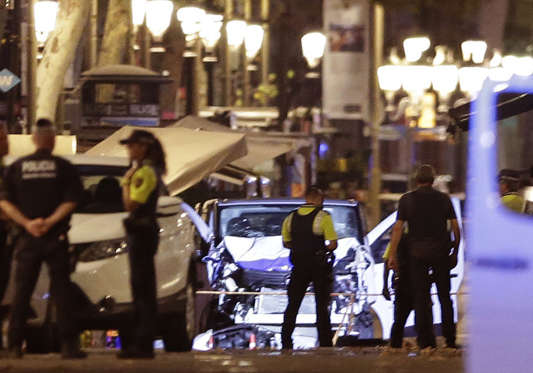Slide 1 of 19: Police officers stand next to the van involved on an attack in Las Ramblas in Barcelona, Spain, Thursday, Aug. 17, 2017. A white van jumped up onto a sidewalk and sped down a pedestrian zone Thursday in Barcelona's historic Las Ramblas district, swerving from side to side as it plowed into tourists and residents. Police said 13 people were killed and more than 50 wounded in what they called a terror attack. (AP Photo/Manu Fernandez)