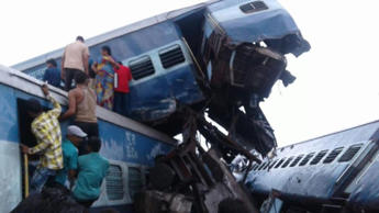 People climb out of the derailed coaches of the Utkal Express that was travelling from Puri to Haridwar.