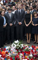 Spain's King Felipe, center, and Queen Letizia, right, pay respects at a memorial tribute of flowers, messages and candles to the van attack victims in Las Ramblas promenade, Barcelona, Spain, Saturday, Aug. 19, 2017. Authorities in Spain and France pressed the search Saturday for the supposed ringleader of an Islamic extremist cell that carried out vehicle attacks in Barcelona and a seaside resort, as the investigation focused on links among the Moroccan members and the house where they plotted the carnage.