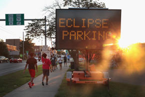 A sign directs visitors to parking areas to view the solar eclipse on August 19,...