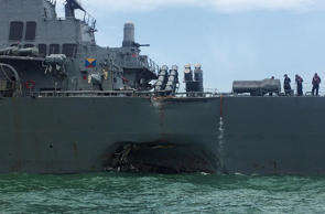 The United States Navy missile destroyer USS John S McCain displaying a hole in its hull as it is towed into the Changi Navy Base off the eastern coast of Singapore, Aug. 21 2017.